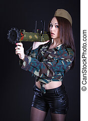 Portrait of a woman in a military uniform with a grenade launche