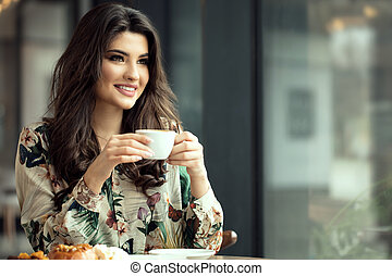 Portrait of a woman in cafe during breakfast.