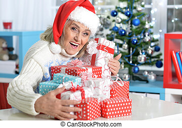 Portrait of a woman in Santa hat with presents