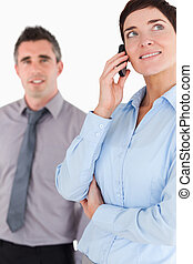 Portrait of a woman on the phone call while her colleague is posing against a white background