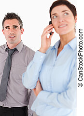 Portrait of a woman on the phone call while her coworker is posing against a white background