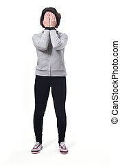 full length portrait of a woman covering face on white background