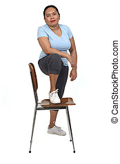 portrait of a  woman playing with a chair looking at camera on white background