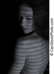 Portrait of a woman posing in darkness with shadow lines of blinds artistic conversion