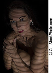 Portrait of a woman posing in darkness with shadow lines of blinds