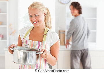 Portrait of a woman posing while a man is washing the dishes