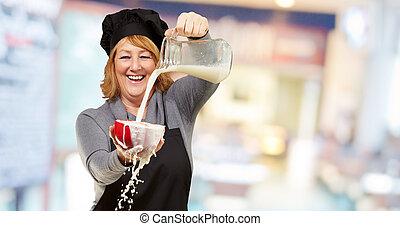 Portrait of a woman pouring milk