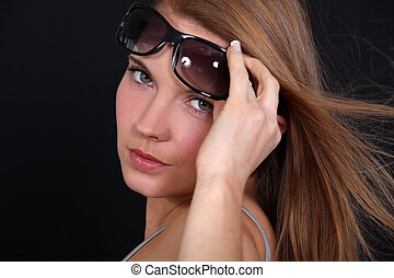 Portrait of a woman raising her sunglasses