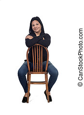 portrait of a woman sitting on a chair in white background, arms crossed