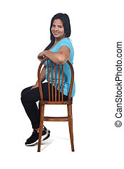 portrait of a woman sitting on a chair in white background, body of profile and looking at camamera