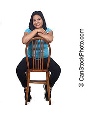 portrait of a woman sitting on a chair in white background, front