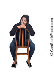 portrait of a woman sitting on a chair in white background, hand on hip