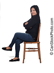 portrait of a woman sitting on a chair in white background, legs and arms crossed ,looking at camera