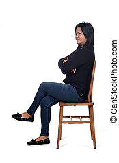 portrait of a woman sitting on a chair in white background, legs crossed and arms crossed