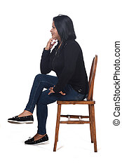 portrait of a woman sitting on a chair in white background, legs crossed and hand on chin