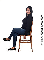 portrait of a woman sitting on a chair in white background, legs crossed and looking at camera