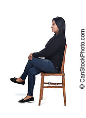 portrait of a woman sitting on a chair in white background, legs crossed