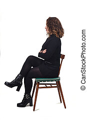 portrait of a woman sitting on a chair in white background, look side and arms crossed
