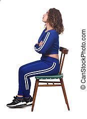 portrait of a woman sitting on a chair in white background, look up, arms crossed