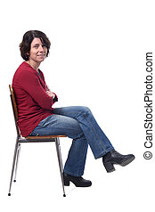 portrait of a woman sitting on a chair in white background, lookig at camera legs and arms crossed