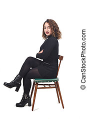portrait of a woman sitting on a chair in white background, looking at camera and arms crossed