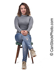 portrait of a woman sitting on a chair in white background, looking at camera and arms