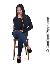 portrait of a woman sitting on a chair in white background, looking at camera and hand on chin