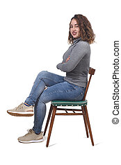 portrait of a woman sitting on a chair in white background, looking at camera and legs and arms crossed