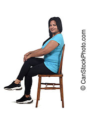 portrait of a woman sitting on a chair in white background, looking at camera and legs crossed