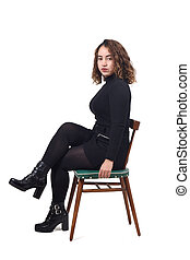 portrait of a woman sitting on a chair in white background, looking at camera and legs crossed serious,
