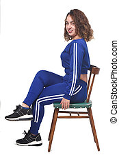 portrait of a woman sitting on a chair in white background, looking at camera, legs crossed