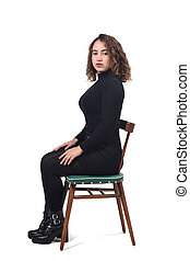 portrait of a woman sitting on a chair in white background, looking at camera, serious,