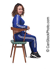 portrait of a woman sitting on a chair in white background, looking at camera,