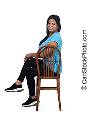 portrait of a woman sitting on a chair in white background, looking at camera