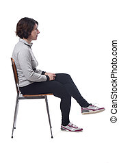 portrait of a woman sitting on a chair in white background, looking to the side and legs crossed
