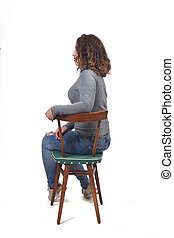 portrait of a woman sitting on a chair in white background, profile