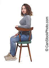 portrait of a woman sitting on a chair in white background, rear view of the chair and looking at camera profile