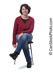 portrait of a woman sitting on a chair on white background, legs crossed