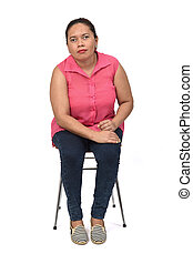 portrait of a woman sitting on a chair on white background, looking at camera