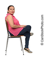 portrait of a woman sitting on a chair with the body in profile and looking at the camera on white background,legs crossed