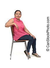 portrait of a woman sitting on a chair with the body in profile and looking at the camera on white background,