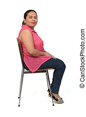 portrait of a woman sitting on a chair with the body in profile and looking at the camera on white background