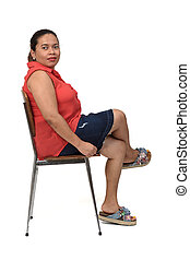 portrait of a woman sitting on a chair with the body in profile and looking at the camera on white,legs crossed