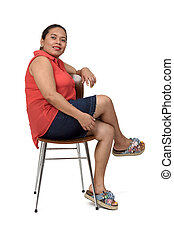 portrait of a woman sitting on a chair with the body in profile and looking at the camera on white background,legs crosse