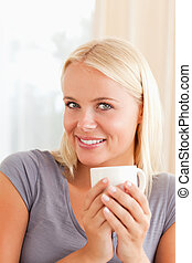 Portrait of a woman sitting on a couch with a cup of coffee