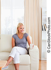 Portrait of a woman sitting on a sofa with a cup of tea