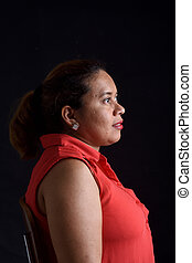 portrait of a woman sitting on chair look side on black background,