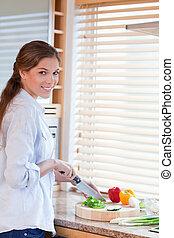 Portrait of a woman slicing pepper