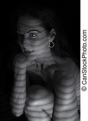 Portrait of a woman standing in darkness with shadow lines of blinds artistic conversion