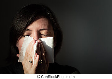 Portrait of a woman suffering from cold blowing her nose in ...